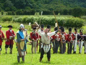 The archers show off their bows while redcoats wait their turn.